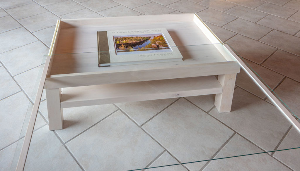 Craig Blacklock worked with Finlayson, Minnesota woodworker, Roger Knudson to create a coffee table to hold and display either the Signature Edition or Museum Edition books along with their accompanying prints. The glass tabletop slides open so you can easily change a page of the open book, or display your prints. A shelf beneath provides storage space for the clamshell boxes. Available in a variety of woods, these are each custom made — starting at $2500. Please call the gallery at 218-485-0478 to place order. Tabletop is 32×48 inches and table is 18 inches high.